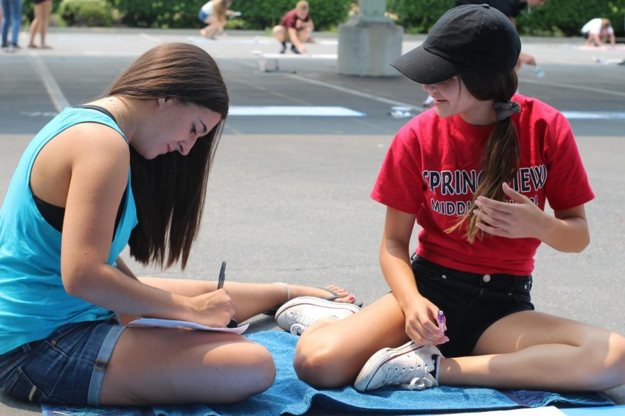 """After meeting each other through leadership last year, Paige Alcala assists Amaia Caballero in painting her movie themed """"Up"""" parking spot. """"We both worked in the pubs committee last year, and we've had a special bond since then,"""" Alcala said. Photo by Haley Bedrin"""