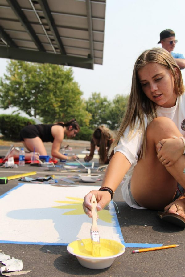 With access to any color, Delaney McGrath paints sunflowers on her spot. Before being able to paint anything, students were instructed to sketch out their design on paper and get it approved.