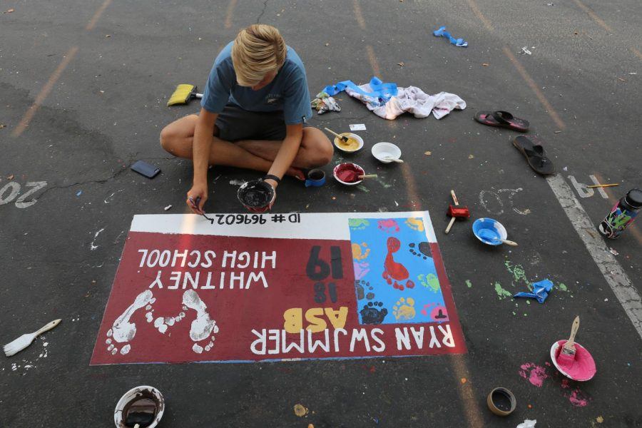 To add the final touches to his senior parking spot, Ryan Walker writes his ID number on the bottom to replicate this year's ASB card design.