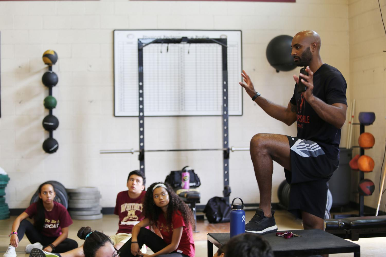 During second period weights training, Mr. John Pichon discusses his goals for the class with his students by explaining the purpose of their workouts. Photo by Aviana Loveall.