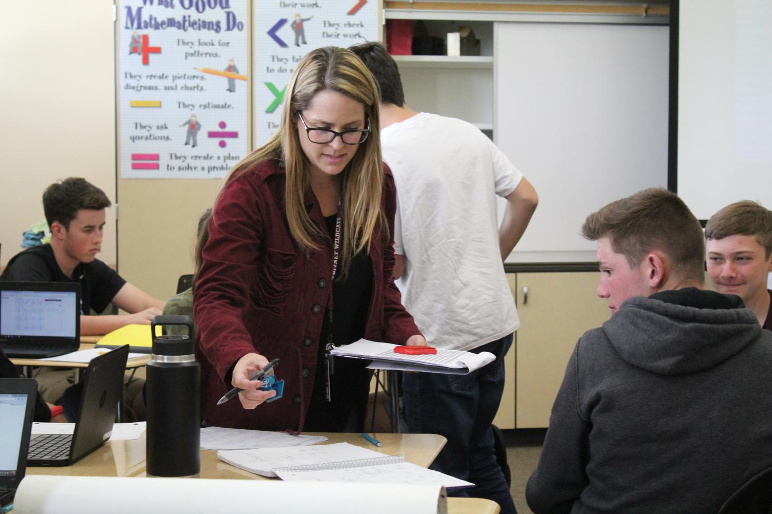 In Ms. Ashley Chaney eighth period Integrated II class, she stamps Eli Brickhandler's homework. Photo by Payton Arthur.