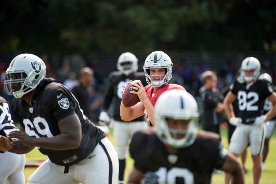 During a preseason practice, quarterback Derek Carr looks on to find a passing target. Photo from Louis Briscese, used with permission under fair use.