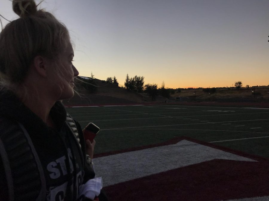 Before the cheer lock-in ends, Reese Phillips watches the sunrise on the football field. The purpose of the lock-in was to bond all three teams together and get ready for Homecoming week. Photo by Emily Pontes.