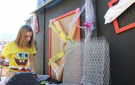 Using the last few hours of Homecoming float construction, Madison Olson works to complete her class' 'haunted manor' themed float. The sophomore class float was haunted hospital, the junior class was haunted cemetery, and the senior class was haunted circus. Photo by Dylan de Valk