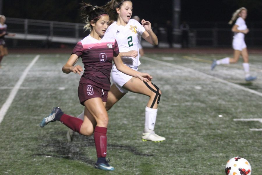 In order to gain possession of the ball, Laney Paduveris rushes toward the ball to outsprint Rylee Roosi from Rio Americano Nov 27.