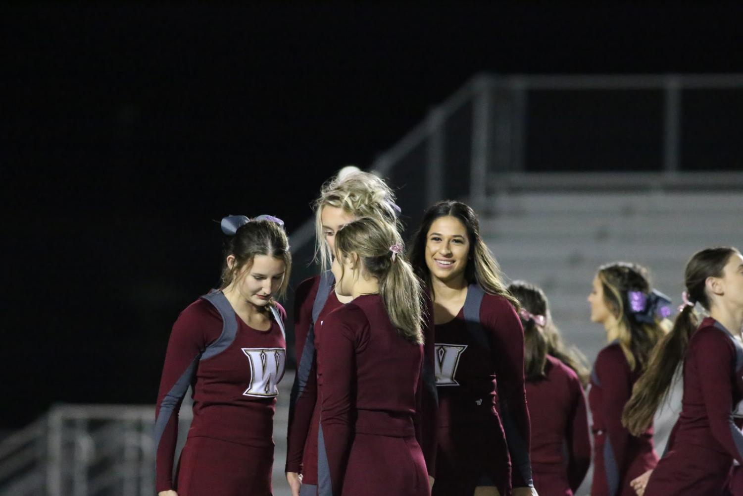 During the last halftime performance of the season Oct. 26, Emily Brustman gets set with her stunt group before partner stunts. This senior night routine was created to focus mainly on the seniors due to this being their last high school game. Photo by Blake Wong.