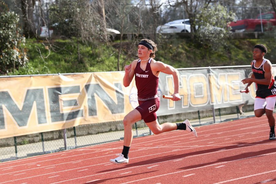 After+receiving+the+handoff+from+his+teammate%2C+Joey+Souto+anchors+the+men%E2%80%99s+varsity+4x100+team.+The+4x100+race+was+a+relay+race+where+four+different+runners+each+run+100+meters.+The+team+placed+second+overall.+Photo+by+Brenden+Jacoby