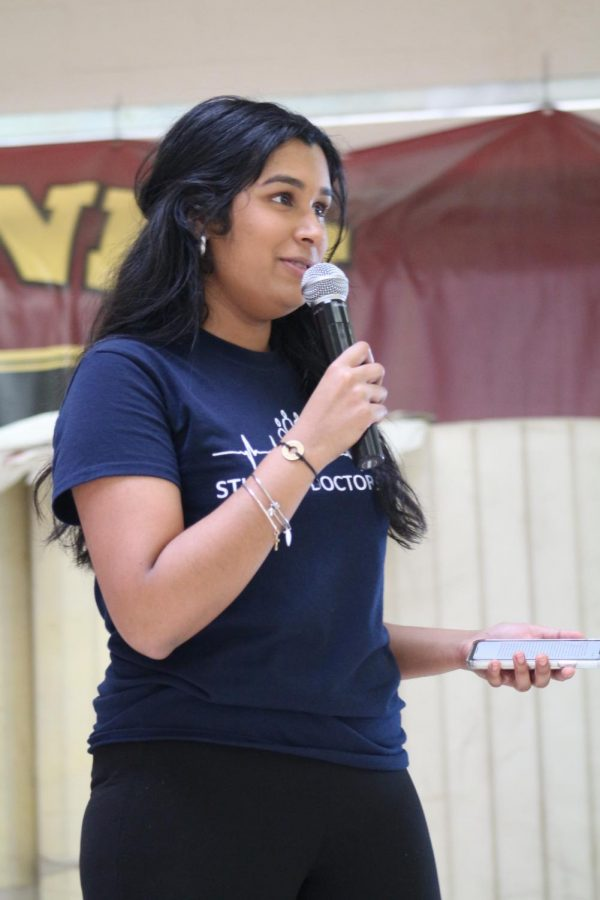 "To kick off the career fair, Hazel Jeyaprakash gives a speech thanking volunteers and attendees. Every professional who presented a booth in the cafeteria March 13 was volunteering their time and supplies they gave away. ""Most importantly, all the donations from this event [are] going to Shriners Childrens Hospital,"" Jeyaprakash said. Photo by Alaina Roberts."
