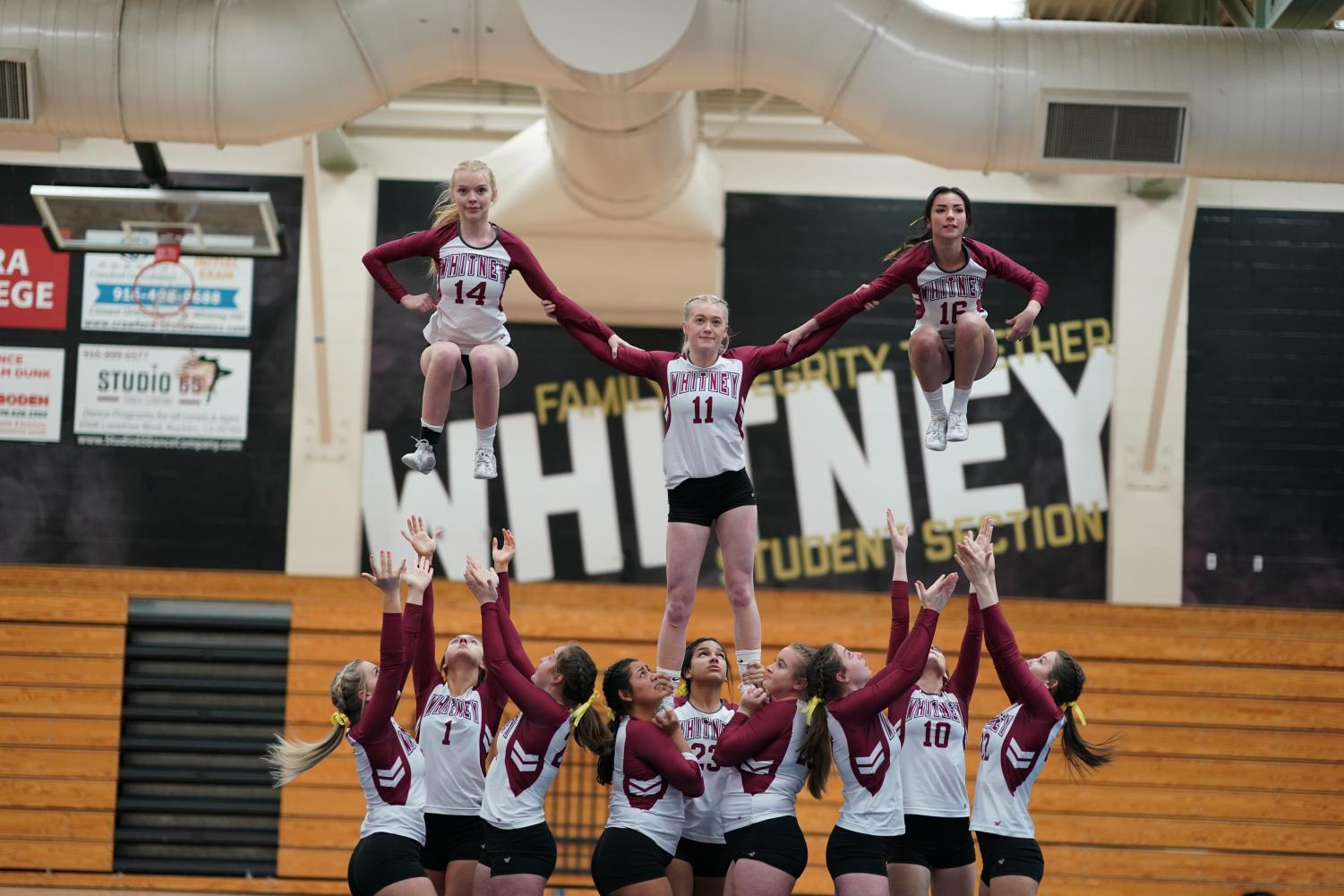 During a league game against Rocklin March 28, Kendra Roberson, Reese Phillips and Elyse Sheek stunt with their groups in Level 2 of pyramids and tosses. They won 15-14. Photo by Geoffrey Clarion.