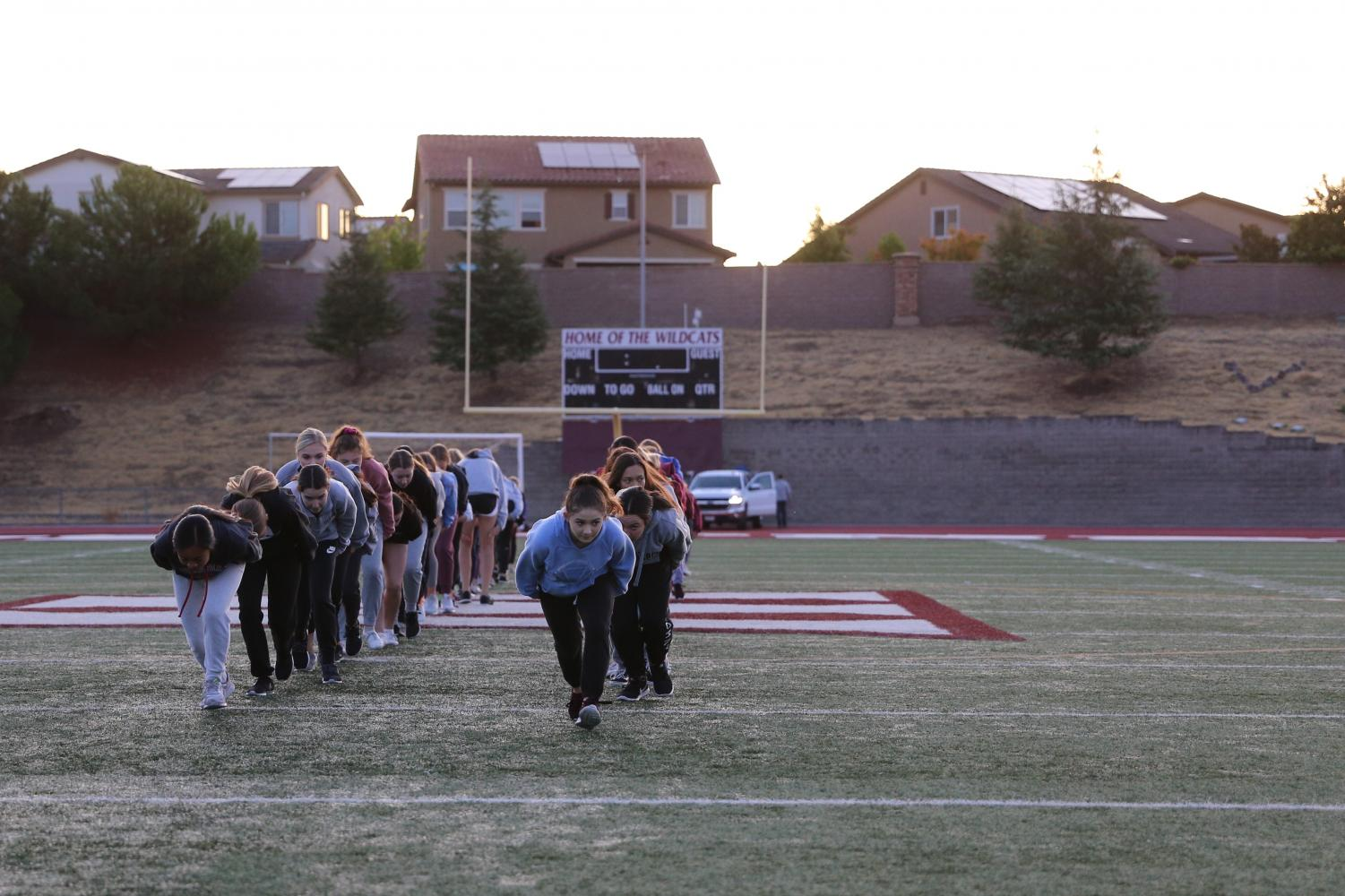 At the combined morning practice Sept. 19, the dance teams run off in two separate lines. Photo by Sofia McMaster