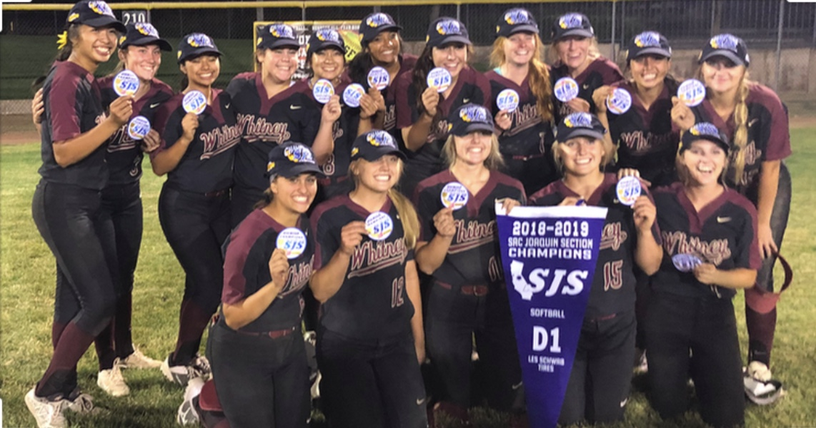 The team is holding up their patches and banner that they received after winning the Division 1 Title.