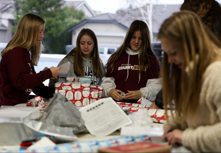 Girls from all levels of soccer meet at Maddie Hamp's house to wrap donated presents Dec. 13. Many of the players also donated gifts themselves. Photo by Sofia McMaster