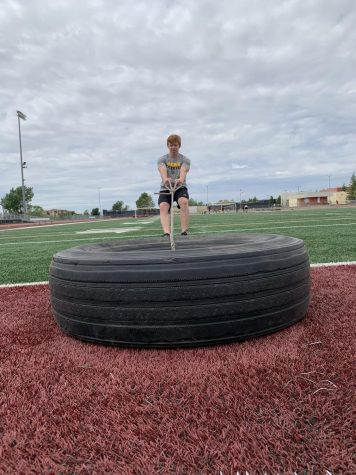 During his workout, May 11, Chris Buck pulls a tire across the football field. Photo by Trinity Barker.
