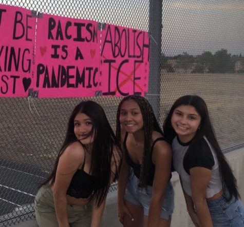 Fabiola Alvarez, Sierra Gladden and Kira Thompson hang anti-racism signs on the Interstate 65 overpass off of Pleasant Grove to support and raise awareness for the BLM movement (image cropped to avoid profanity). Photo by Angela Roberson.