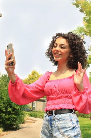 Adalie Bucher waves while FaceTiming her friends outside. Photo by Grace Trammell.