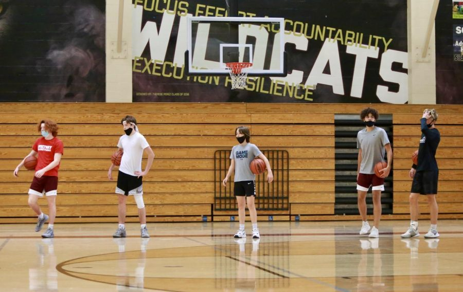 At the start of practice, the JV team lines up to start running drills Oct. 6. Players were placed in pods of 10 and they rotate between three stations over the course of practice. They spend 30 minutes with Coach John Pichon in the weight room, 30 minutes with Coach Nick French and Coach Shawn Andrews in the main gym working on fundamentals, and then 30 minutes with Coach Alex Anderson and Coach Chris Purdy working on shooting and attacking the basket. Photo by Paulina Solorzano