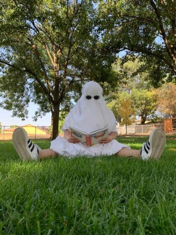 Melanie Garcia dresses as a ghost while reading a book for a TikTok-inspired photoshoot. Photo by Elisha Tapangan.