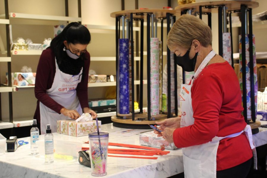 Local volunteers wrap gifts Nov. 27 as part of the Bayside gift wrapping station in the Westfield Galleria mall.